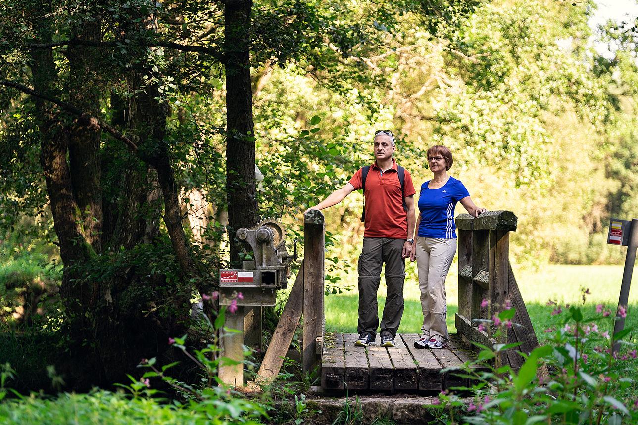 Zwei Wanderer auf einer Brücke über der Wondreb.