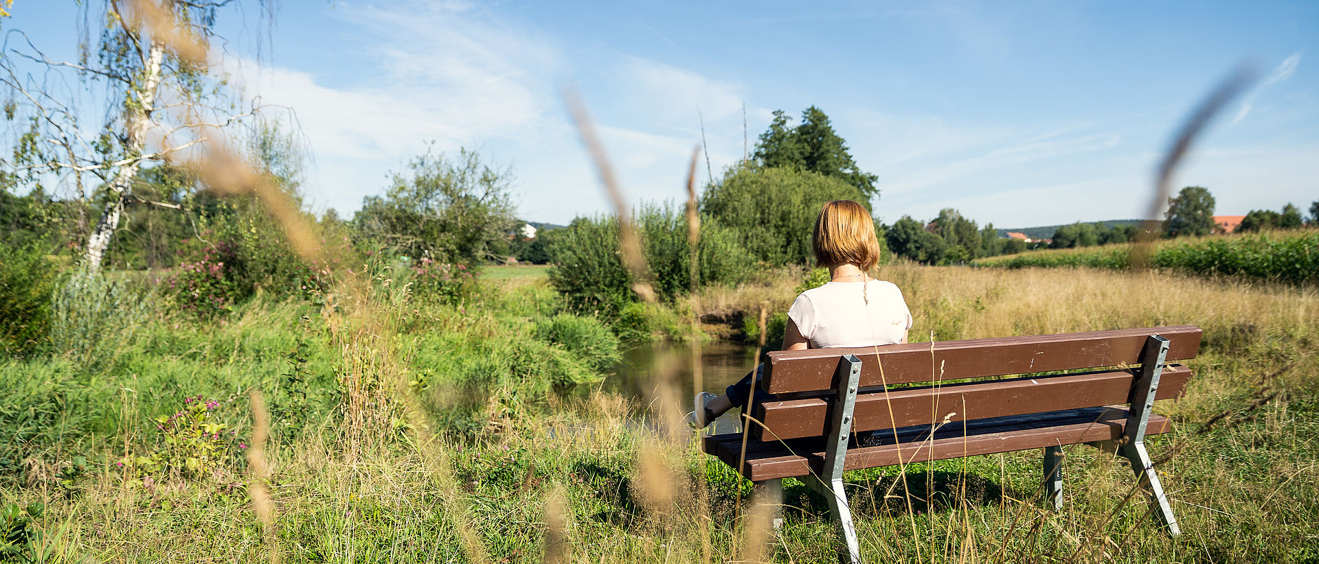 Eine Frau sitzt auf einer Bank mit Blick auf Waldsassen.