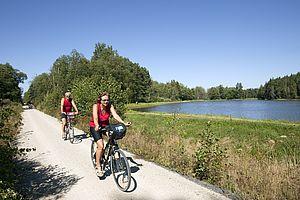 Fahrradfahren entlang eines Sees.