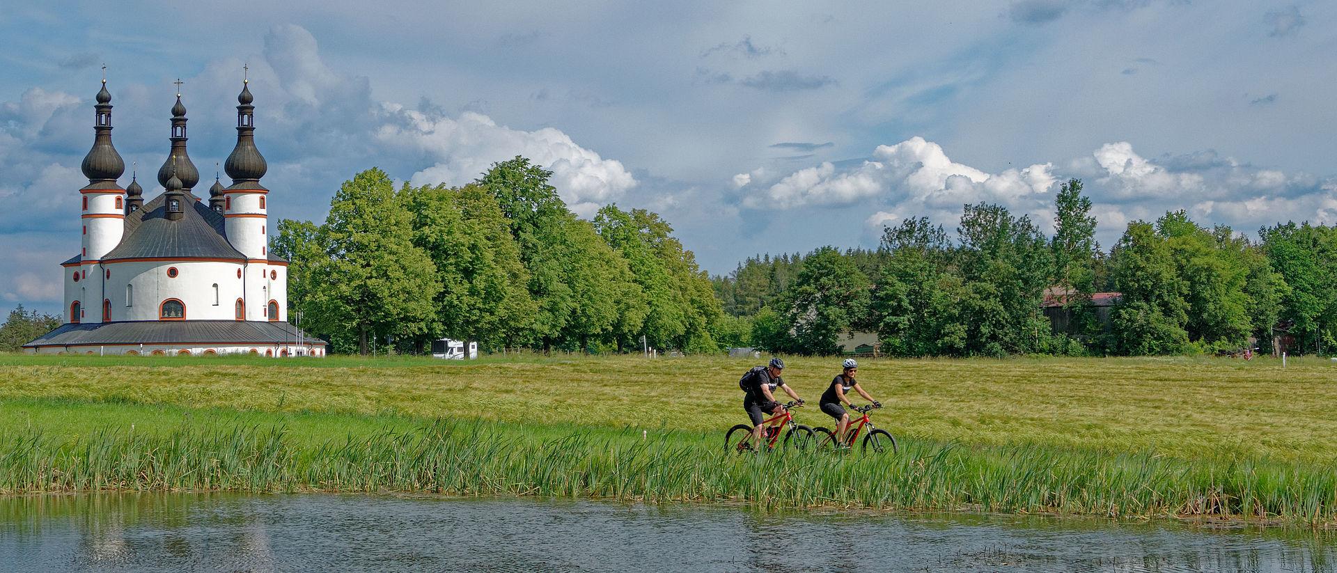 Zwei Fahrradfahrer auf einer Wiese mit Kappl im Hintergrund.